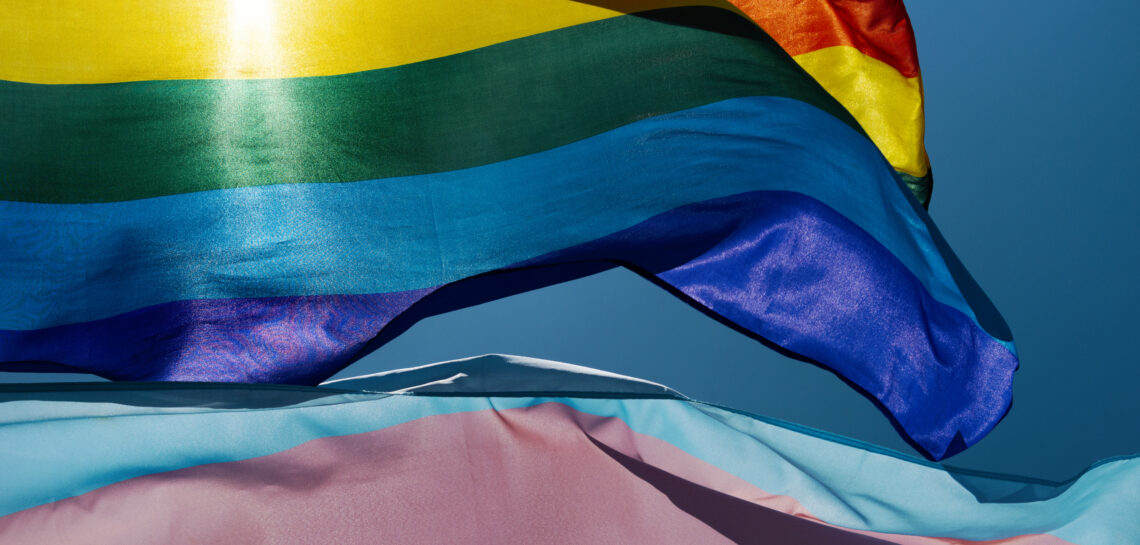 gay and transgender pride flags waving on the sky